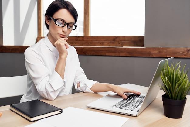 Kobieta w kostiumie przed laptopem dokumentuje profesjonalne światło pracy w tle