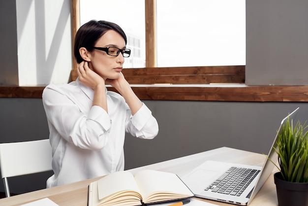 Kobieta w kostiumie przed laptopem w okularach pewność siebie studio styl życia