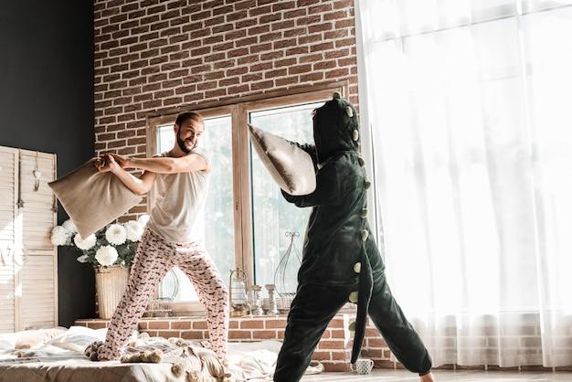Kobieta w kostiumowej poduszce walczy z jej mężem w domu