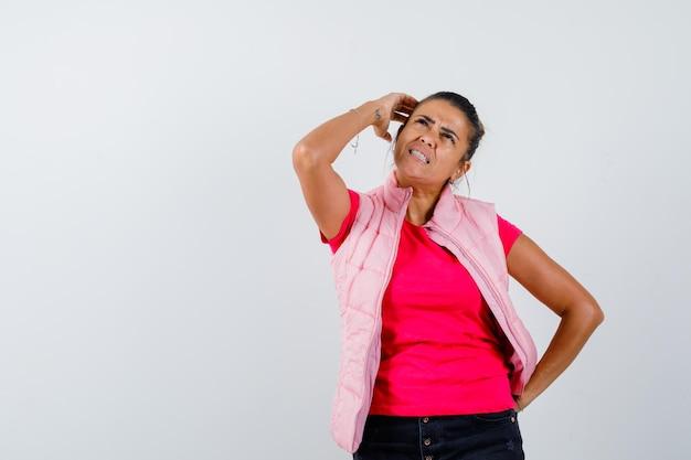 Kobieta w koszulce, kamizelce drapiącej się po głowie i wyglądająca na zapominalską