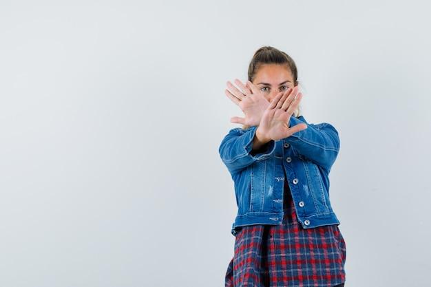 Kobieta w koszuli, kurtce, pokazując gest stop i patrząc poważnie, widok z przodu.