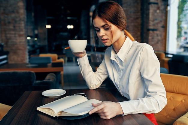 Kobieta w koszuli przy stole w kawiarni