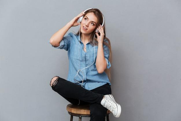 Kobieta w koszuli siedzi na krześle i słuchanie muzyki