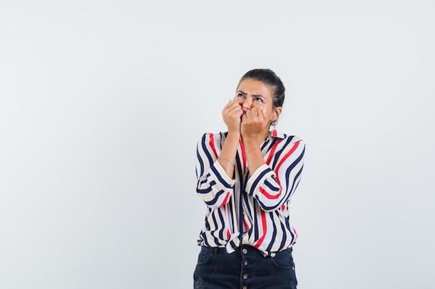Kobieta w koszuli, spódnica trzymająca pięści na twarzy i wyglądająca na wzburzoną