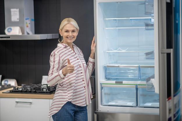 Kobieta w koszuli w paski, demonstrując nową lodówkę w salonie