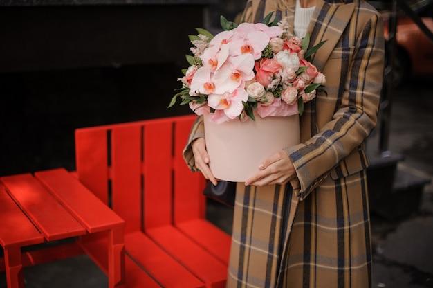 Kobieta w kraciasty płaszcz jesień trzyma różowe pudełko kwiatów