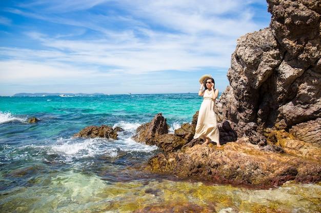 Kobieta w kremowej sukience stoi, ciesząc się pięknym morzem na plaży.