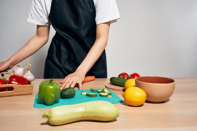 Kobieta w kuchni do krojenia warzyw na białym tle