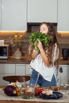 Kobieta w kuchni gospodarstwa zielone świeże aromatyczne pietruszki liście. młoda gospodyni gotuje. zdrowe odżywianie, wegetariańskie jedzenie, dieta i koncepcja ludzi. do utraty wagi i detoksykacji. pionowy