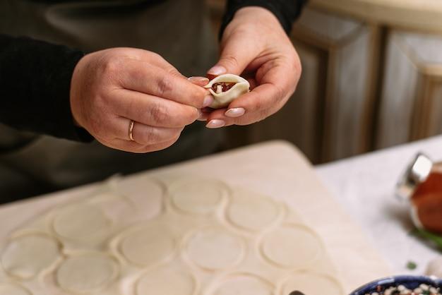 Kobieta w kuchni rzeźbi domowe pierogi lub półprodukty. kucharz owija mielone mięso wołowe w ciasto