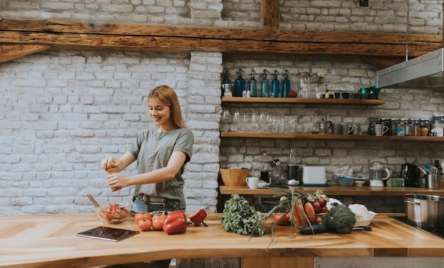 Kobieta w kuchni używa pastylka czytelniczego przepis