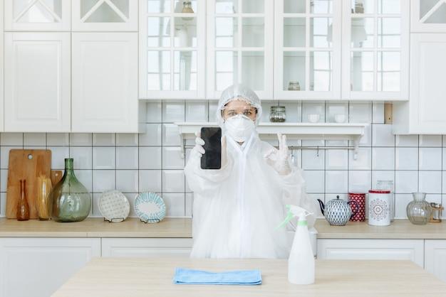 Kobieta w kuchni ze sprzętem ochrony osobistej przed covid-19, pokazująca swój telefon