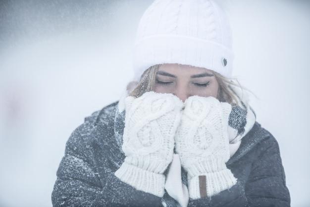 Kobieta w kurtce i czapce zimowej jest przymarznięta do kości, ogrzewając dłonie w rękawiczkach, oddychając na nie.