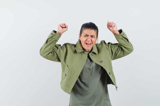 Kobieta w kurtce, koszulce pokazującej gest zwycięzcy i wyglądającej błogo