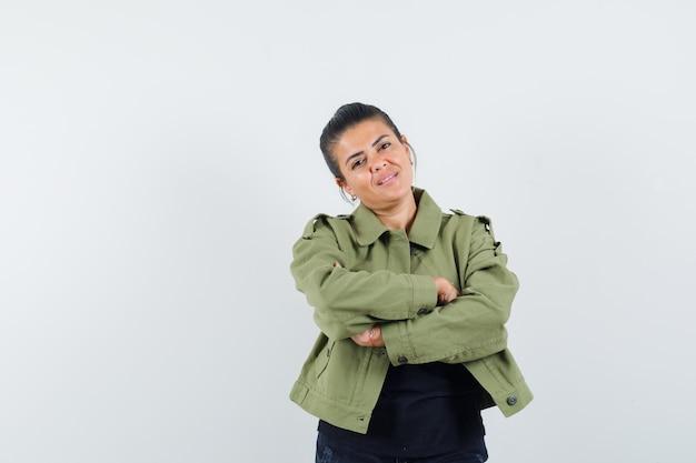 Kobieta w kurtce, koszulce stojącej ze skrzyżowanymi rękami i wyglądającej pewnie