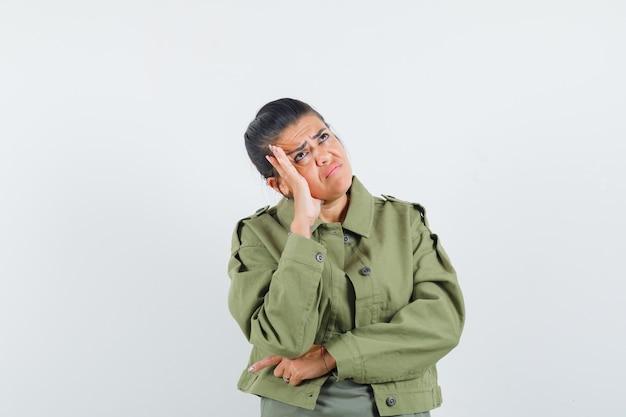 Kobieta w kurtce, koszulce, trzymając dłoń na policzku i patrząc smutno