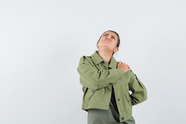Kobieta w kurtce, koszulce, trzymając rękę na ramieniu i zamyślona