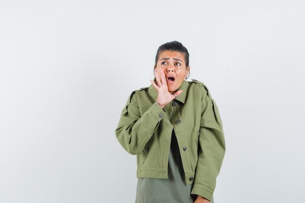 Kobieta w kurtce, koszulce trzymającej rękę w pobliżu otwartych ust i wyglądająca na zaskoczoną