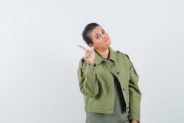 Kobieta w kurtce, koszulka skierowana w lewy górny róg i wyglądająca na pewną siebie