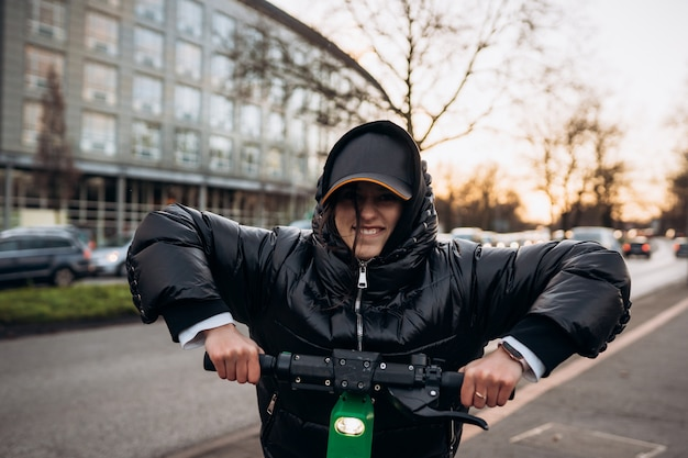 Kobieta w kurtce na skuterze elektrycznym w jesiennym mieście. jazda pojazdami elektrycznymi w zimne dni.