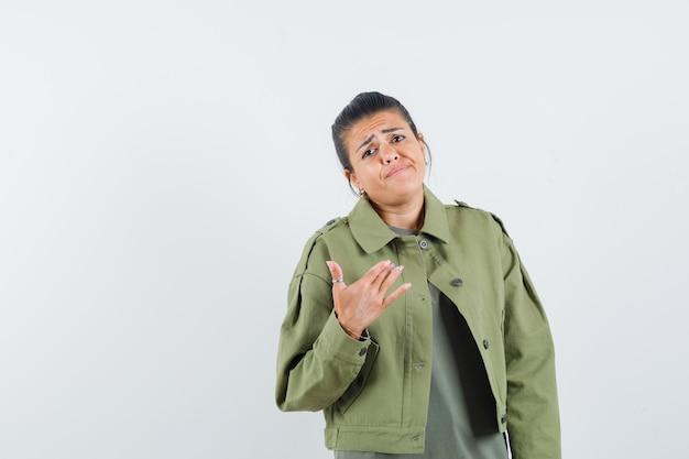 Kobieta w kurtce, t-shirt pokazująca się i wyglądająca na zdezorientowaną