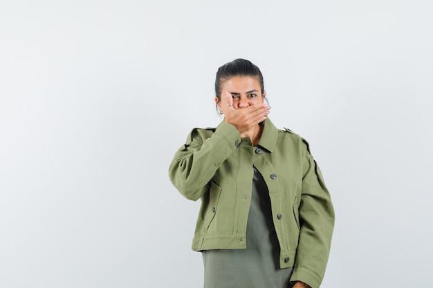 Kobieta w kurtce, t-shirt, trzymając dłoń na ustach i wyglądająca na przestraszoną