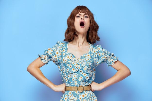 Kobieta w kwiatowej sukience z otwartymi ustami, rękami na pasku modna fryzura na lato