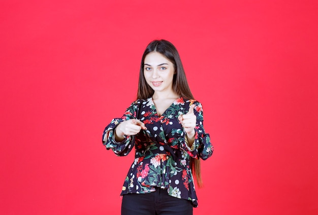 Kobieta w kwiecistej koszuli stojąc na czerwonej ścianie i zauważając osobę z przodu.