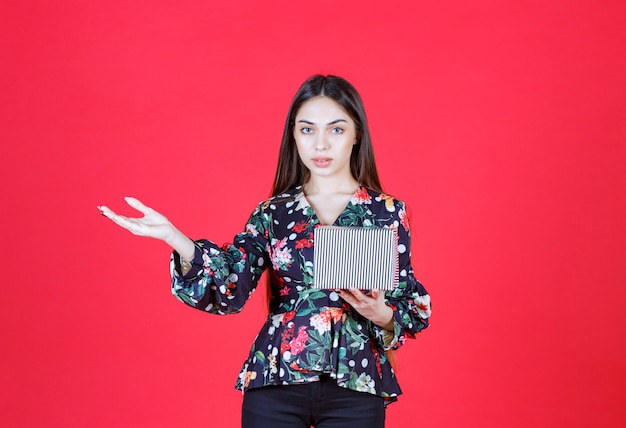 Kobieta w kwiecistej koszuli trzymająca srebrne pudełko i zapraszająca kogoś do obsługi.