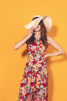 Kobieta w kwiecistej sukni i kapeluszu