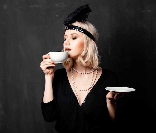 Kobieta w latach dwudziestych ubrania z filiżanką kawy