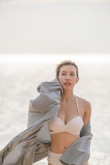 Kobieta w latającym szlafroku spacery po plaży z tłem morza.