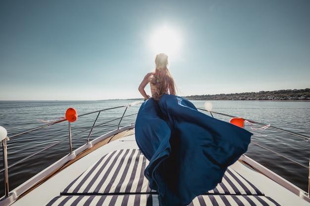 Kobieta w lataniu piękną niebieską sukienkę na łodzi