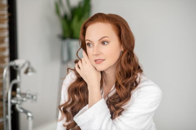 Kobieta w łazience. ładna kobieta z długimi rudymi włosami wygląda na zrelaksowaną