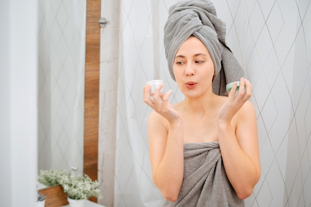 Kobieta w łazience ze zdziwieniem trzyma słoik kremu nawilżającego do twarzy i ciała. koncepcja pielęgnacji ciała.