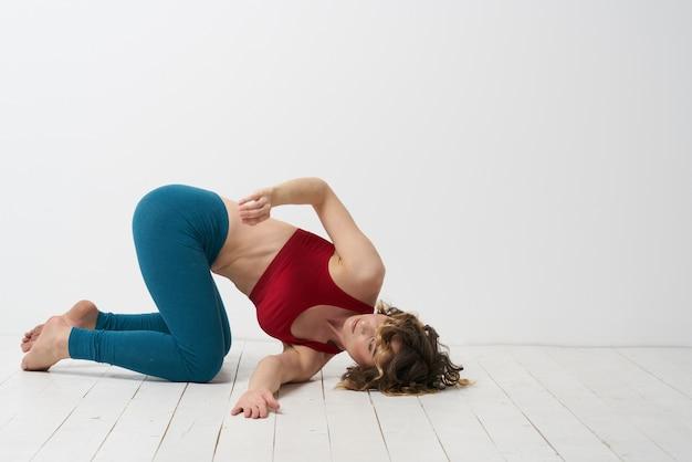Kobieta w legginsach jest zaangażowana w gimnastykę w jasnym pomieszczeniu sport fitness szczupła sylwetka.