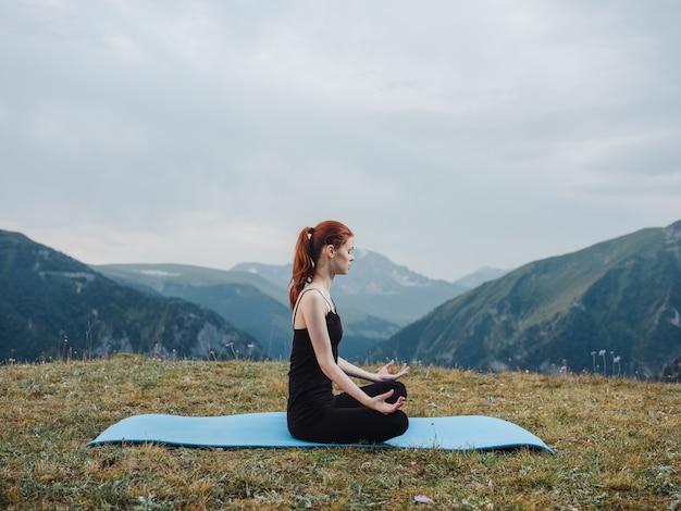 Kobieta w leginsach medytuje siedząc na dywanie na łonie natury w górach. wysokiej jakości zdjęcie