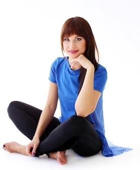 Kobieta w leginsach, siedząc na podłodze