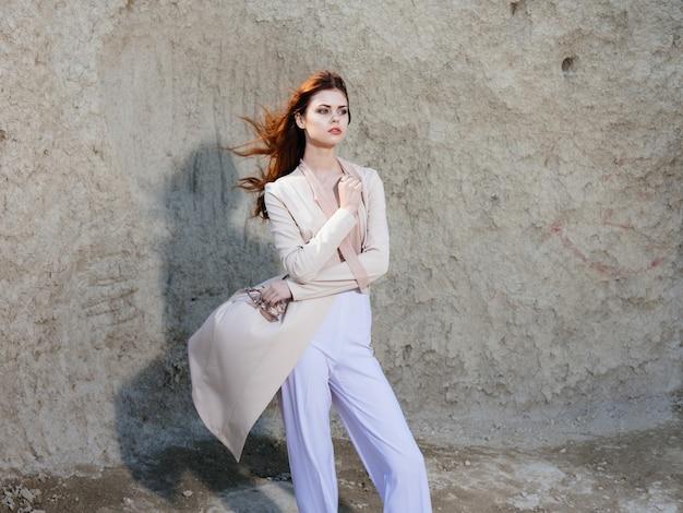 Kobieta w lekkich ubraniach w pobliżu skał w naturze na zewnątrz