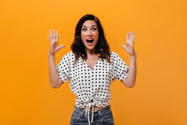 Kobieta w lekkiej bluzce krzyczy radośnie i patrzy w kamerę na pomarańczowym tle. cudowna dorosła dziewczyna w koszulce w groszki i dżinsach jest bardzo zaskoczona.