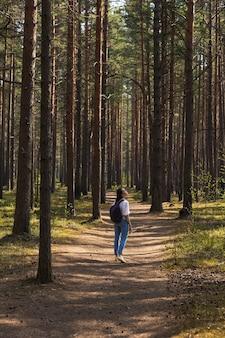 Kobieta w lekkiej koszuli i dżinsach spacerująca po drewnianej ścieżce w naturze