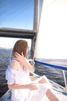 Kobieta w lekkiej odzieży i kieliszek wina w rękach pływa na jachcie wzdłuż rzeki