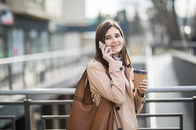Kobieta w lekkim płaszczu spaceru ulicą trzymając filiżankę i telefon