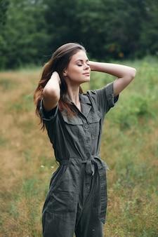 Kobieta w lesie idąc przez pole czerwone włosy zielony garnitur przycięty widok