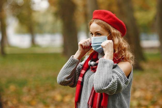 Kobieta w lesie jesienią. osoba w masce. motyw koronawirusa. pani w czerwonym szaliku.