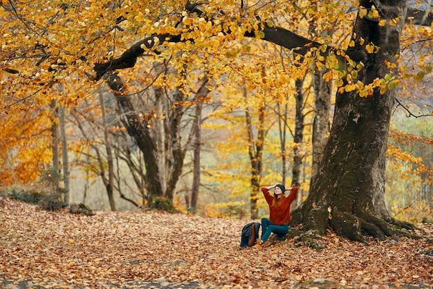 Kobieta w lesie jesienią siedzi pod drzewem z żółtymi liśćmi model parku krajobrazowego