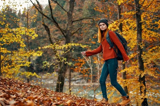 Kobieta w lesie jesienią w pobliżu rzeki krajobraz żółte liście turystyki