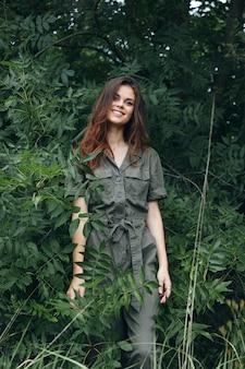 Kobieta w lesie piękny uśmiech w zielonym kombinezonie podróży przycięty widok