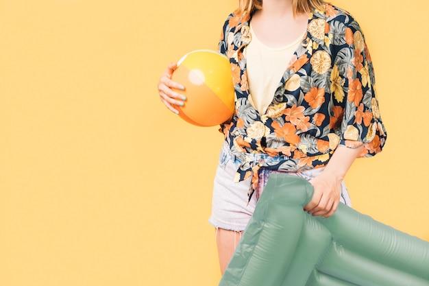 Kobieta w letnich ubraniach trzymająca nadmuchiwaną matę i piłkę plażową