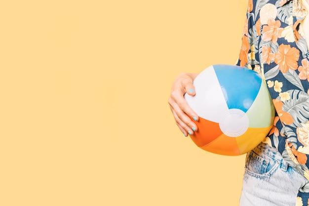 Kobieta w letnich ubraniach trzymająca nadmuchiwaną piłkę plażową